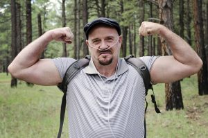 Middle aged man flexes his muscles as he hikes in the woods wearing therapeutic oxygen.