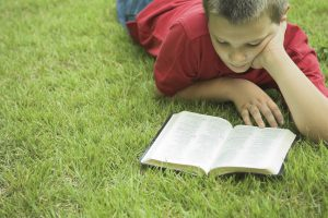 Young boy reading a bible outside.