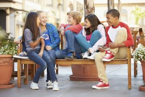 Group Of Children Sitting On Bench In Mall Smiling And Laughing At Each Other Holding a Moblie Phone