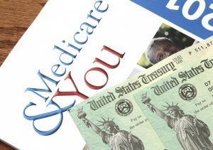 West Palm Beach, USA - July 17, 2014: A US government publication that explains Medicare benefits, entitled Medicare and You, lies on a desk. Two US Treasury checks of the type used to pay Medicare and Social Security benefits are partially visible on top of it.