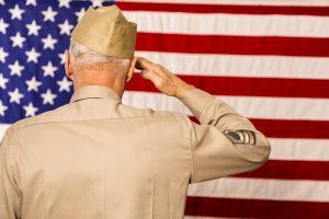 Senior man, army veteran saluting the 50-star USA flag. He wears a WWII military uniform. Patriotism.