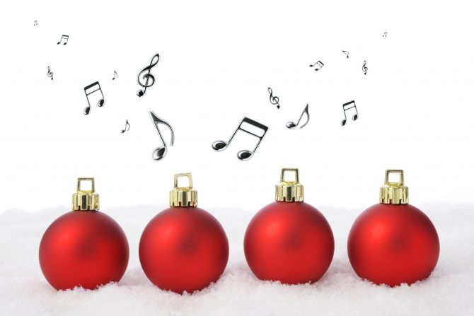 Four red Christmas balls on the snow with flying musical note against white background.