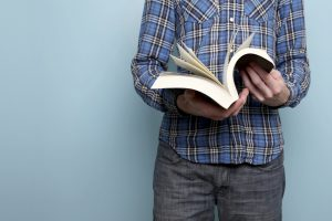 Male in blue plaid shirt reading a book