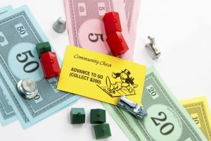 Houston, TX, USA - November 1, 2014: Monopoly board game - Advance To Go card, money, playing pieces