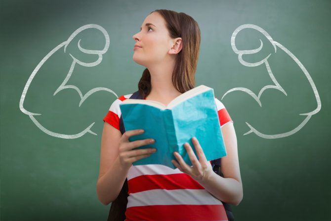Student reading book in library against green chalkboard