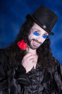 Vertical colour studio shot on dark blue backdrop of male vampire in top hat and blue tinted glasses, smiling showing fangs, holding a red rose. Curly black hair, black beard and mustache, black satin poet's shirt.