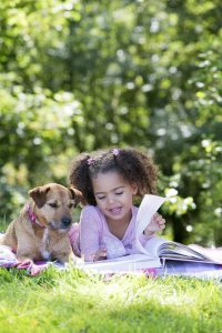 A happy little girl lies down on her front in her garden with her dog by her side. She is reading a book to her dog and smiling.