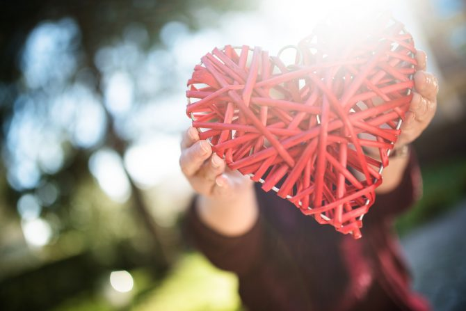 holding an wooden heart for st. valentine