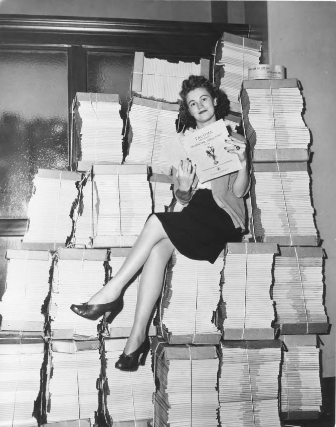 Image of a woman on top of a pile of phone books