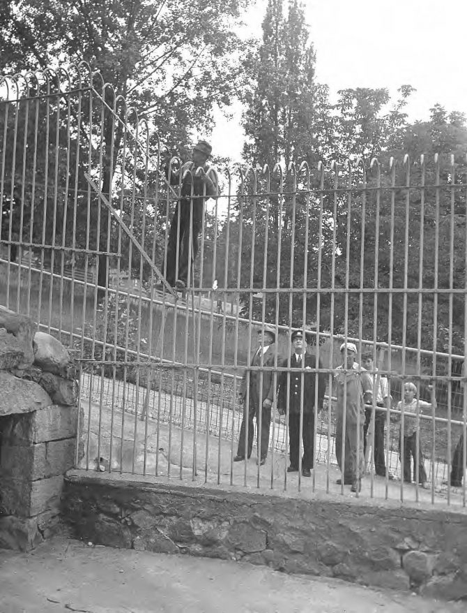 Image of men around a steel fence